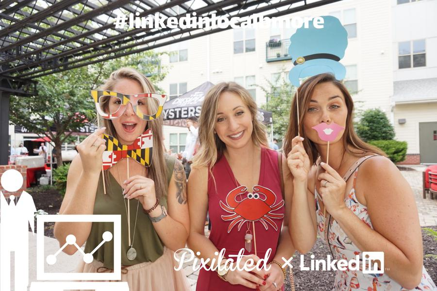 Three women pose with photo booth props at a LinkedInLocal event in Baltimore, MD.