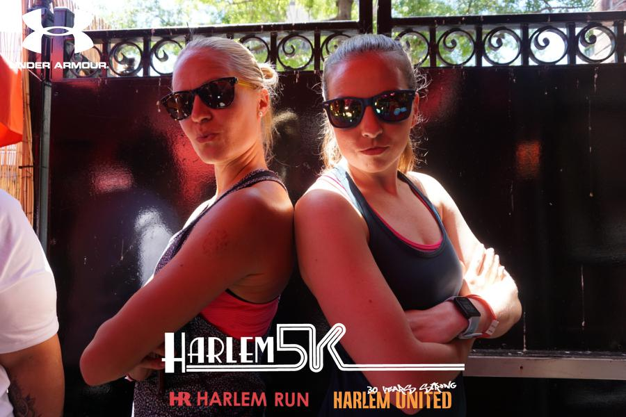 Two woman pose in a PixiCam photo kiosk at the Harlem 5k in 2018.
